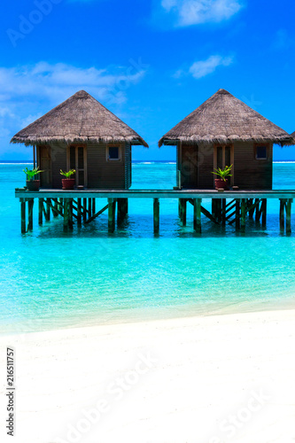 Poster Turquoise Water villas on wooden pier in turquoise ocean on the white sand beach