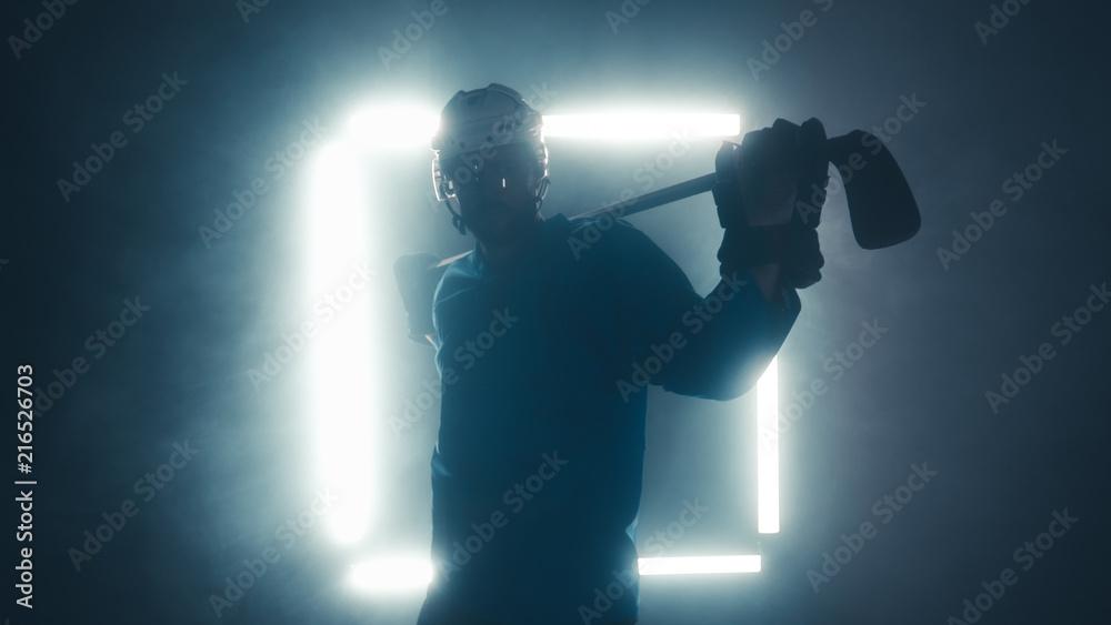 Fototapeta Portrait of Caucasian male ice hockey player in uniform, looking into the camera, dramatic lighting
