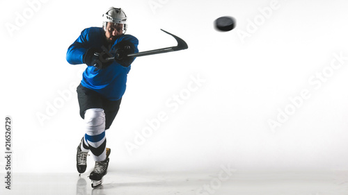 Portrait of Caucasian male ice hockey player in uniform performing a slap shot against white background