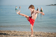 funny little happy boy raised his leg to kick on sand near sea beach in summer