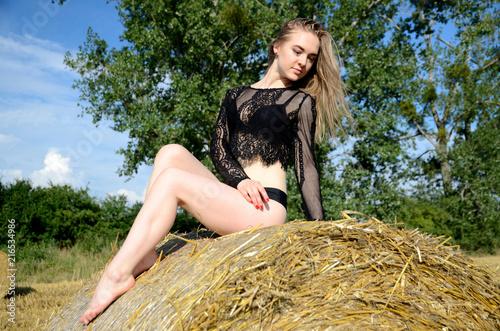 Valokuvatapetti Girl sits on bale of hay