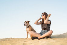 Beautiful Young Woman In Sunglasses With Dog Sit On Sand. Girl In Hiking Casual Clothes And Staffordshire Terrier Puppy Sitting On Sandy Beach Or In Desert On Hot Sunny Day