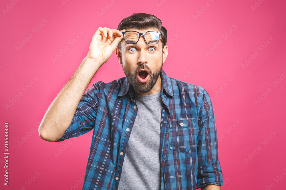 Fototapeta OMG! It's incredible! Portrait of handsome young man in glasses looking at camera while standing against pink background. Close up portrait of bearded man keeping his mouth open.
