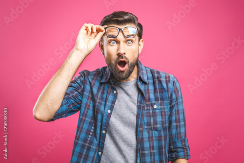 Fotografie, Tablou OMG! It's incredible! Portrait of handsome young man in glasses looking at camera while standing against pink background