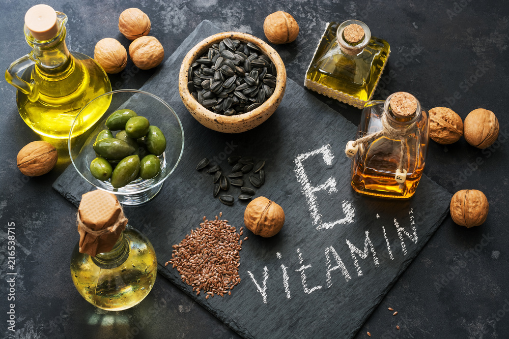 Fototapety, obrazy: Food rich in vitamin E. A set of different oils. Seeds of flax, sunflower, walnut, olives. Top view.