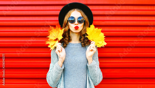 Cool girl autumn portrait woman with yellow maple leaves on a red background - 216540371