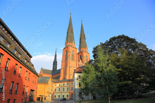 Amazing view on old historical cathedral with green trees on front and blue sky on background. Uppsala, Sweden, Europe. Beautiful backgrounds