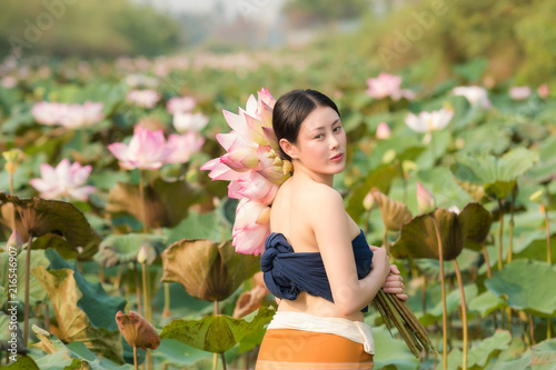 Beautiful women is collecting lotus pods in lotus garden.