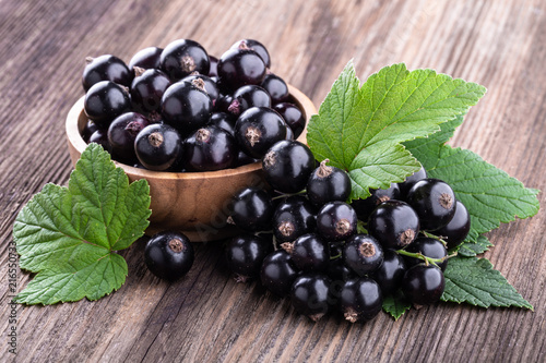 Fresh ripe black currant in wooden bowl with original leaves on rustic old backg Canvas Print