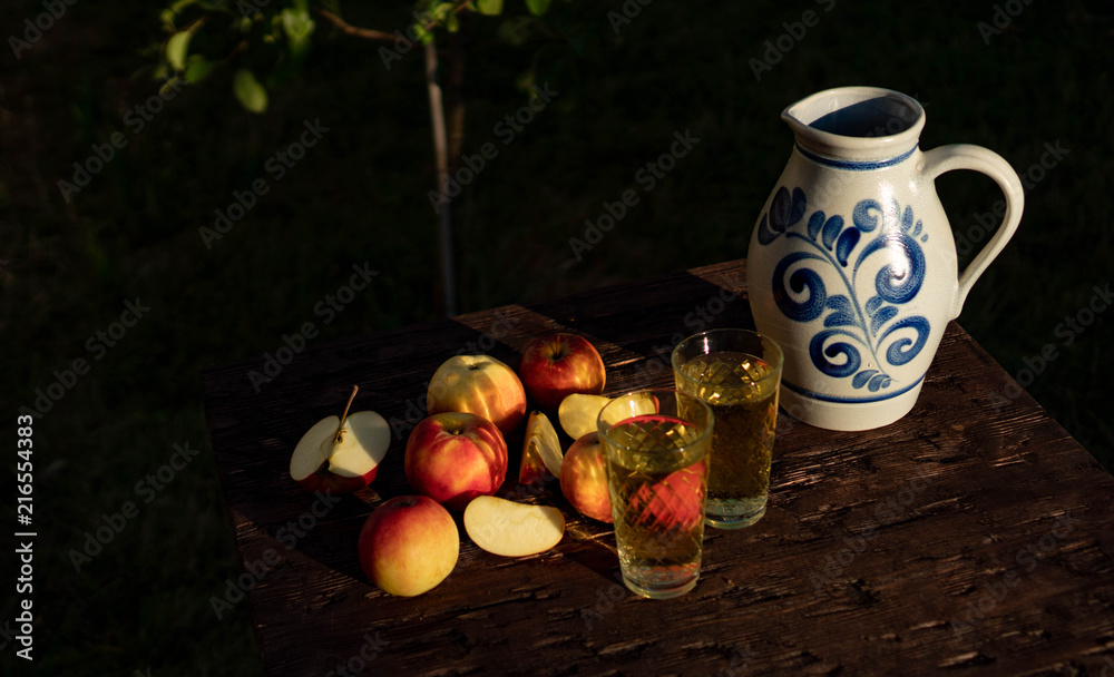 Fototapety, obrazy: Traditional apple wine in the city of Frankfurt in Hesse. A jug of wine is on an old wooden table in the garden, around it are apples