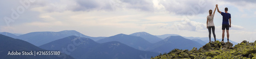 Back view of young tourist couple, athletic man and slim girl standing with raised arms holding hands on rocky mountain top enjoying fantastic panorama. Tourism, traveling and climbing concept.