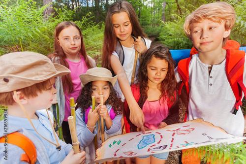 Fototapeta Kids with map on treasure hunt navigation activity