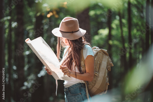 фотографія  Woman standing among trees at sunset and searching way on location map for her t