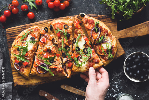 Flatbread pizza garnished with fresh arugula on wooden pizza board, top view. Dark stone background. Person picking slice of pizza