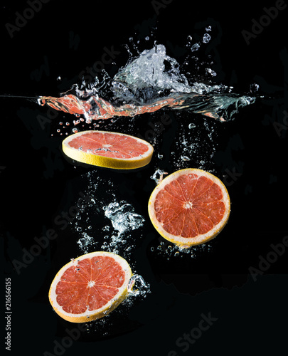 Fresh grapefruit slice dropped into water. Black background