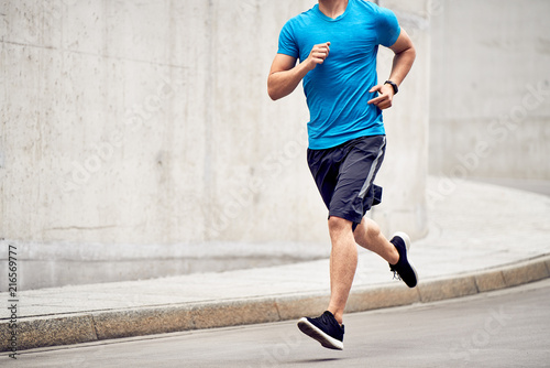 Poster Jogging Athletic man jogging on road in the city. Sport and fitness concept