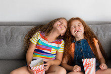 Young Girls Making Silly Faces With Pop Corn In Their Mouth
