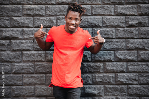 Mockup, african man model showing empty red t-shirt against brick wall