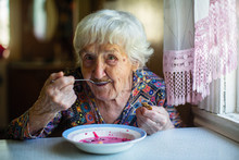 An Elderly Woman Eating Soup B...