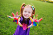 red-haired girl preschooler shows palms stained with multicolored finger paints