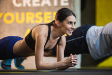 Focus On Smiling Lady Enjoying Planking. She Is Balancing On Elbows During Abs Workout In Sport Studio. Man Is Doing Same Exercise On Background