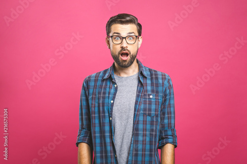 Fototapeta Indoor shot of amazed excited man doesn`t believe his success, keeps hands on head, stares at camera, says omg or wow
