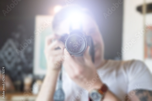 Obraz A man takes pictures on a camera with a flash - fototapety do salonu