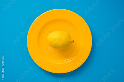 Fotografie, Obraz  Top view of lemon on bright yellow plate on blue background/diet concept