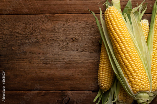 Fototapeta Fresh corn on cobs on rustic wooden table, closeup. Top view with copy space obraz