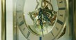 Sunshine filters through the glass enclosure to the internal workings of a lovely bright brass mechanical table clock.