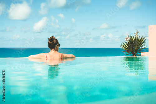 Woman relaxing on vacation in infinity edge swimming pool ...