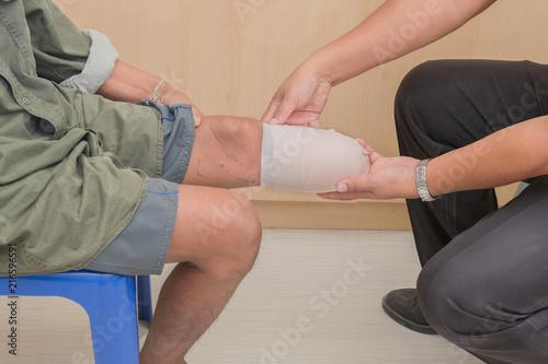 below knee stump bandaging, amputee BKA with prothesis preparing Wallpaper Mural