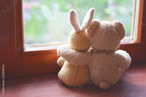 Tablou Canvas Best friends teddy bear and bunny toy sitting on brown window sill hugging each other and looking out of window on vintage tone