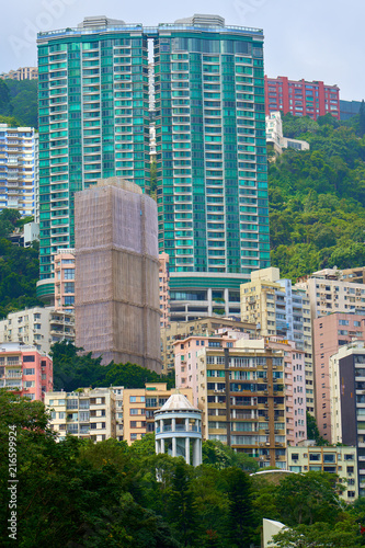 Cityscape of construction site with scaffolding wrapped in safety mesh (debris netting) among high-rise residential buildings on hillside.