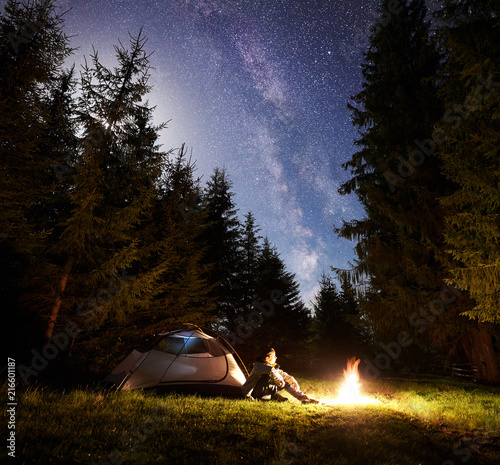 Fototapeta Camping site at night. Tourist tent on forest clearing and male hiker sitting in front of burning bonfire under night blue starry sky on pine trees background. Beauty of nature and tourism concept. obraz na płótnie