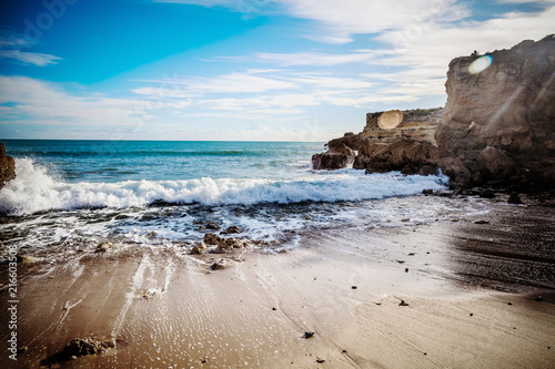 Beautiful coast of the ocean, Algarve, Portugal. Waves break against the rocks in the sun