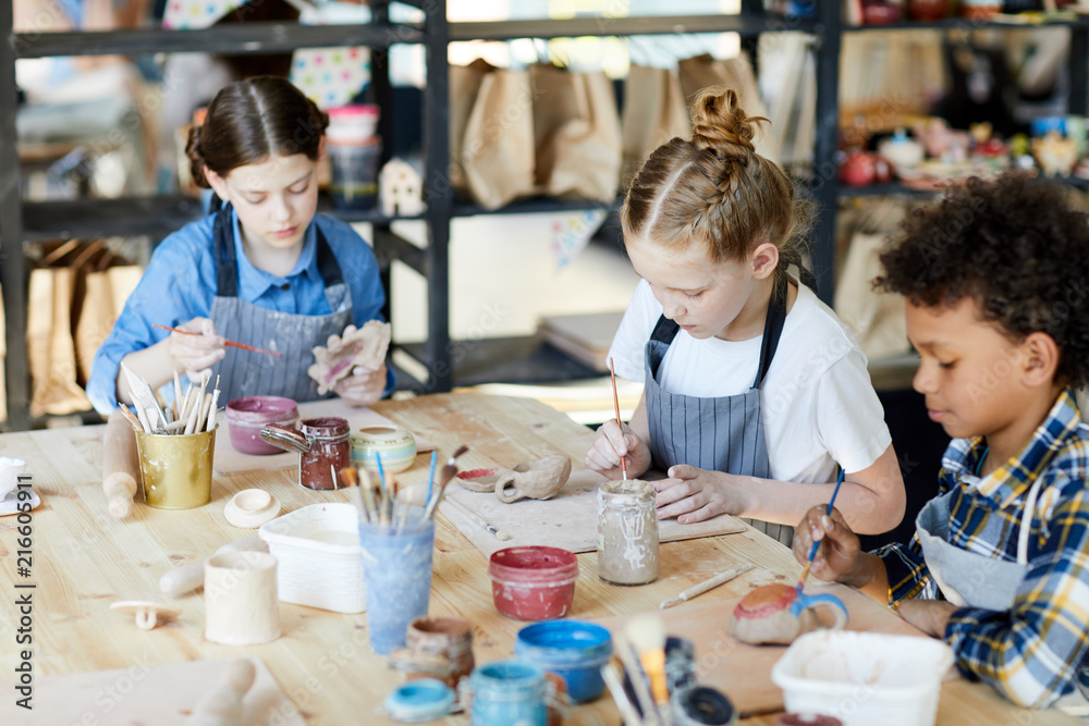 Fototapety, obrazy: Group of diligent schoolkids sitting by table while making and painting self-made earthenware