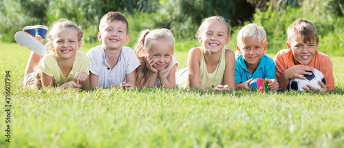 Fotografía  Group of friendly kids lying on green grass in park