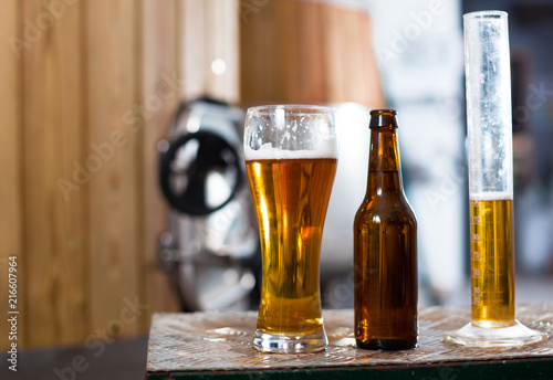 Spoed Foto op Canvas Bier / Cider bottle and glass with gold beer on the background of barrels for fermentation