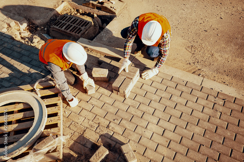 High angle of workers in white helmets arranging a paving stone Canvas