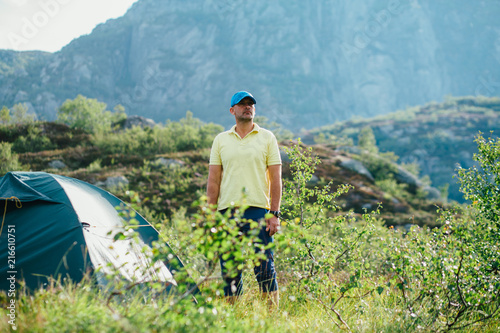 Hiker man standing near camping tent in wild Norway mountains in summer morning Poster