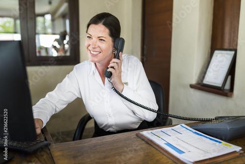 Obraz na plátne Female resort receptionist working at the front desk