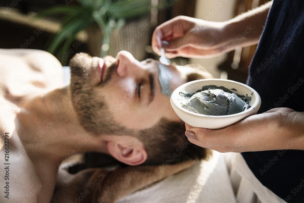 Fototapeta Man getting a mud mask at a spa