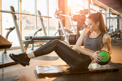 Female fitness model exercising with medicine ball at gym. Canvas Print