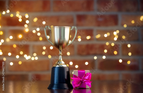 Foto handmade gift box with purple bow and golden prize cup on wooden table with fair
