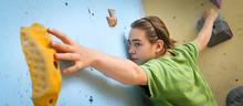 Teenage Boy Training On Climbing Wall