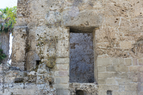 Foto op Plexiglas Oude gebouw the stone wall of the ancient limestone building with a doorway. Side, Turkey