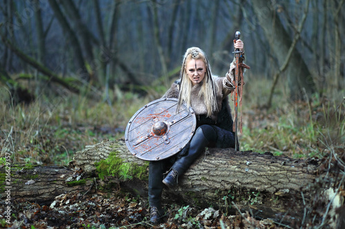 Fotografie, Obraz  Blonde northern warrior woman in forest with shield and sword in hand covered in blood