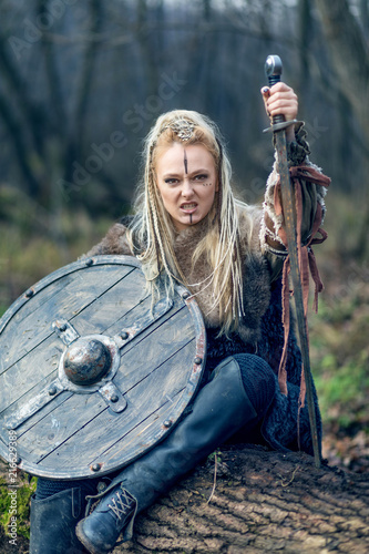 Photo  Blonde young beautiful viking warrior woman in forest with shield and sword in hand