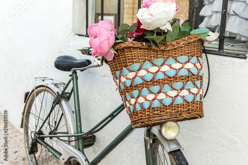 Deurstickers Fiets Vintage bicycle parked with basket of beautiful flowers. Old bike on the street leaning on the perimeter with window